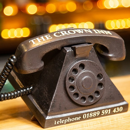 Old style phone with pub phone number on it